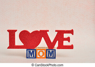 The words love mom spelled with alphabet blocks against a white background