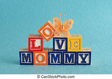 The words love mommy spelled with alphabet blocks against a blue background with a orange butterfly