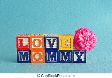 The words love mommy spelled with alphabet blocks against a blue background with a pink flower