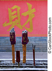 "The words ""Wealth"" written on the wall, worship of incense, in t"