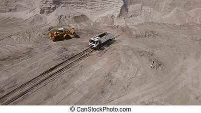 Loading, transportation and unloading of sand from the quarry by a loader into the body of a dump truck. on a sunny day. aerial view, frame from a drone