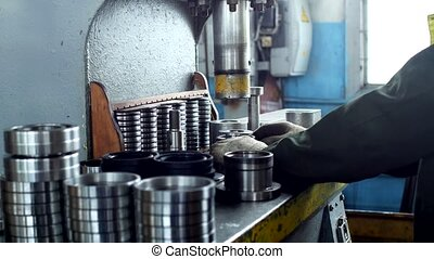 The worker assembles the pressing of the bearing into a...