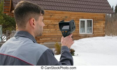 The worker carries out an inspection of the house the thermal imager. To look for losses of heat. Fight against heatlosses. Energy saving.