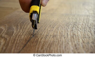 the worker cuts off the linoleum with a utility...