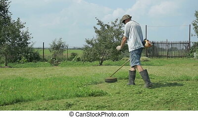 The worker cuts the grass with lawn string trimmer