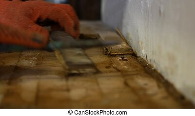 The worker dismantles the parquet floor.