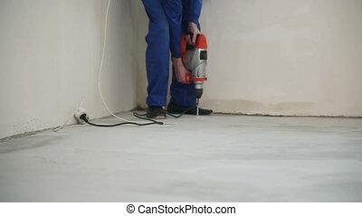 The worker drills the floor