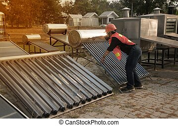 The worker in uniform and helmet checks concentrating Solar Power with Flat Plat collector and Evacuum Tube Collector.