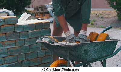 The Worker Loads a Colored Paving Stone in the Wheelbarrow....
