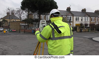 The worker measures the distance with a theodolite. -...