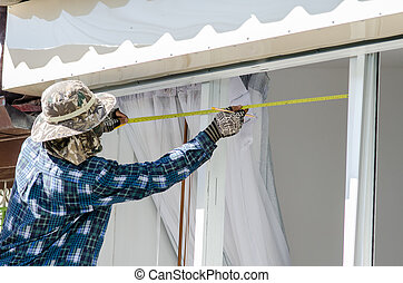 The worker measuring tape window outdoor.