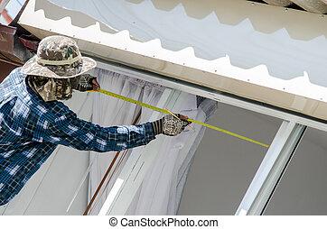 The worker measuring tape window outdoor.