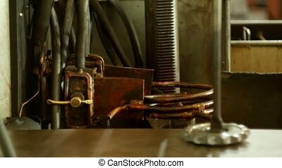 The worker prepares and adjusts the machine for hardening ...