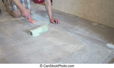 The worker prepares the floor for tiling - male worker...