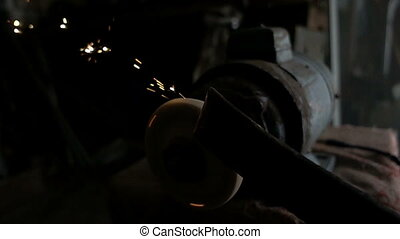 The worker sharpens the tool. Work on a sharpening machine.