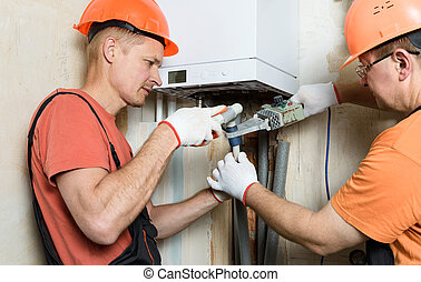 The workers are soldering plastic pipes of gas boiler.