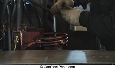 The working specialist prepares equipment for hardening and ...