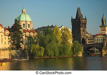 The world famous Charles Bridge pictured here at sunset spans the Vltava River in Prague.