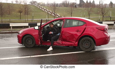 The wounded girl is sitting in a broken car after a car accident on a wet road.