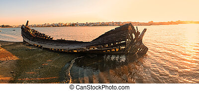The wrecks of a burned boat on the bank of the Seixal Bay in the evening light. Lisbon. Portugal