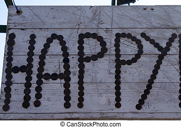 the written happy on a wooden background