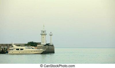 The yacht is near the lighthouse