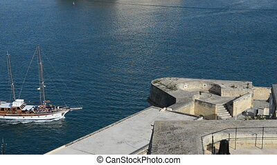 The yacht moves in harbour, Valetta, Malta
