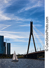 The yacht with a sail at the cable-stayed bridge in Riga