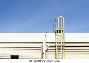 The yellow fire escape stair attach at the factory building with the blue sky