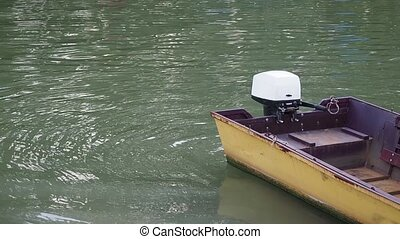 The yellow fishing boat with outboard motor.