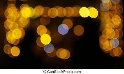 The yellow lights of the garlands in the defocus blink like...