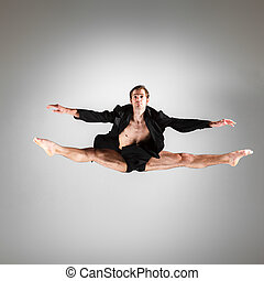 The young attractive modern ballet dancer jumping on white...
