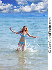 33cf1dcb541e Young woman in blue denim jumpsuit walking to the sea. Young woman ...