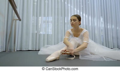 The young ballerina binds her point toes sitting on the...