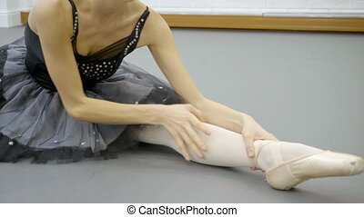 The young ballerina is doing split and inclining to her led...