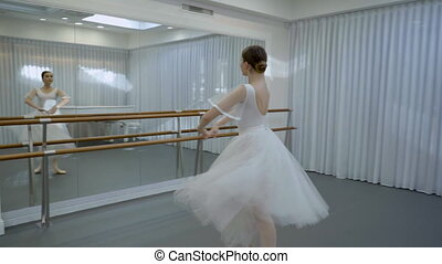 The young ballerina trains to do fouette in front of the...