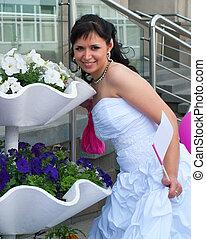 bride in a wedding dress against flowers