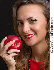The young beautiful girl in a scarlet dress eats apple - The...