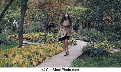 The young beautiful girl walks in the park
