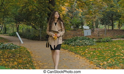 The young beautiful girl walks in the park.
