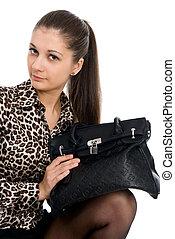 The young beautiful girl with a black handbag
