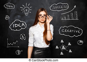 The young beautiful girl with glasses in a white blouse on the background of business icons and diagrams. The concept of a successful business woman