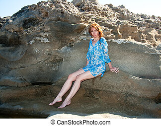 The young beautiful woman in a natural sea swimming bath among stones.