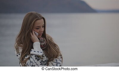 The young beautiful woman is talking on the mobile phone concentrated on the conversation listening with all her attention.