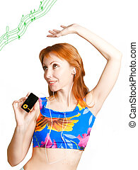 The young beautiful woman listens to music through an...