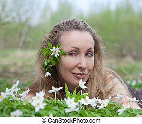 The young beautiful woman on a glade of blossoming snowdrops in the early spring