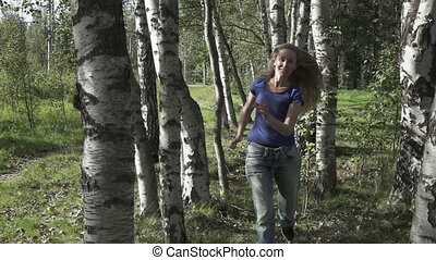 the young beautiful woman runs in the birch wood