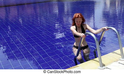The young beautiful woman swims in pool
