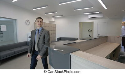 The young businessman is looking for the room to rent in modern office building and female secretary assists him.