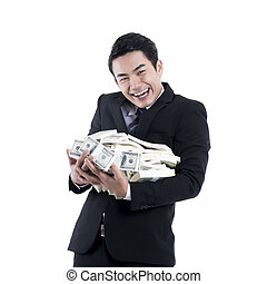 The young businessman smiling and holding a big pile of dollars